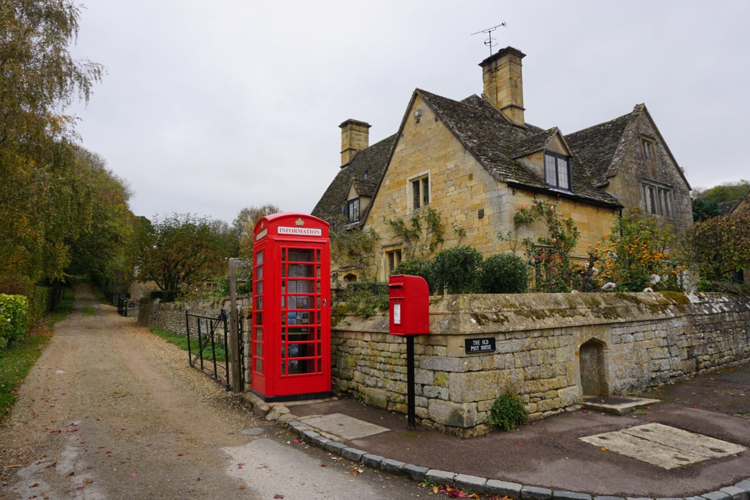 Bright red telephone box and post box contrast against the honey-coloured Cotswold cottage in Stanton